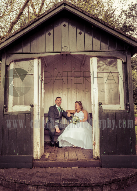Surrey wedding photographer- bride and groom sat in shed