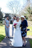 Surrey wedding photographer / St Johns Church Coulsdon Wedding / The bride hugging mum with bridesmaids in the background