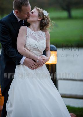 Surrey Wedding Photographer-  weald of kent golf club weddings, bride and groom kissing outside venue