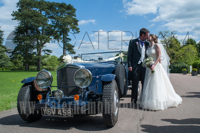 Surrey wedding photographer - Hartsfield Manor- Bride and Groom in kissing by wedding car