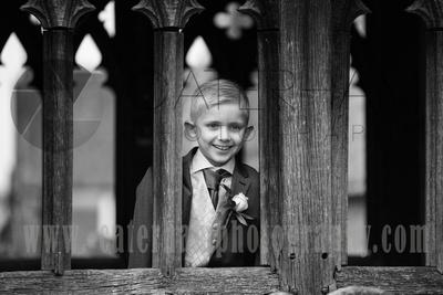 Surrey Wedding Photographer- St Nicholas Church Godstone- Page Boy at Old Fanshioned window in Church Wedding Venue