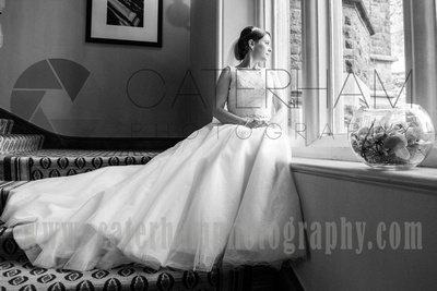 Surrey wedding photographer - Hartsfield Manor- Bride looking out of window