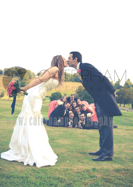 Surrey wedding photographer- Woldingham Golf Club- bride and groom kissing with bridesmaids and groomsmen together