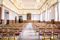 surrey wedding photographer- kingston county hall- bride and groom walking down chairs- ceremony room