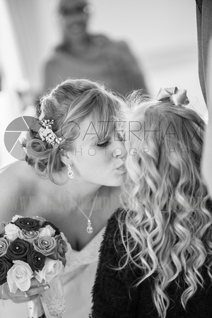 Romantice wedding -Surrey wedding photographer/ Bride kissing kids cheek - black and white photography