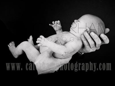 New Born Photographer-  Surrey photographer - cute baby being held