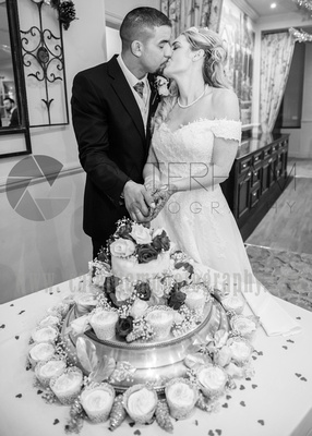 Surrey Wedding Photographer-  Reigate manor hotel- the bride and groom cutting the cake