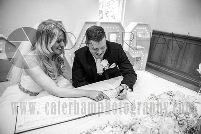 Surrey Wedding Photographer- Wedding Venue Mulberry House Weddings-Bride and Groom happily signing the register after their wedding ceremony