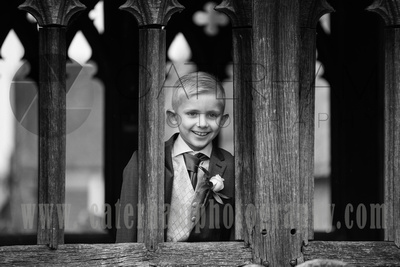 Surrey Wedding Photographer- St Nicholas Church Godstone- Page Boy at Old Fanshioned window in Church Wedding Venue