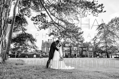Surrey wedding photographer - Hartsfield Manor- Wonderful wedding venue with Bride and Groom kissing in front