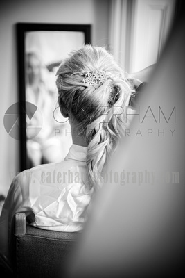 Surrey wedding photographer- Bridal Preparation- bride looking at hair