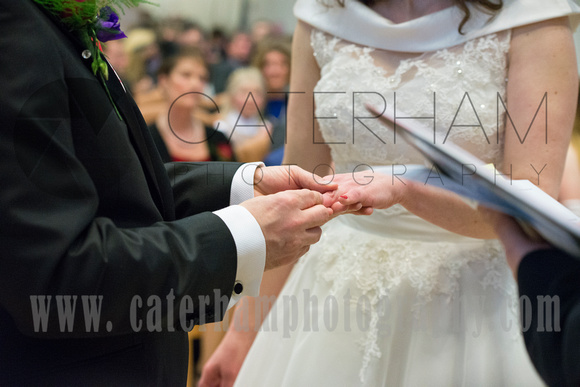 Surrey wedding photographer- St Paul's Church Addlestone- Groom puts the ring on Braids hand